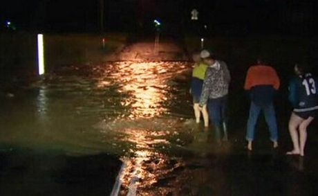 Laidley residents check levels as water flowed over streets yesterday.