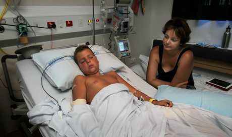 Jodie Carlyle watches over her son Marcus, 8, who is recovering after becoming impaled on a branch in a motorbike crash.