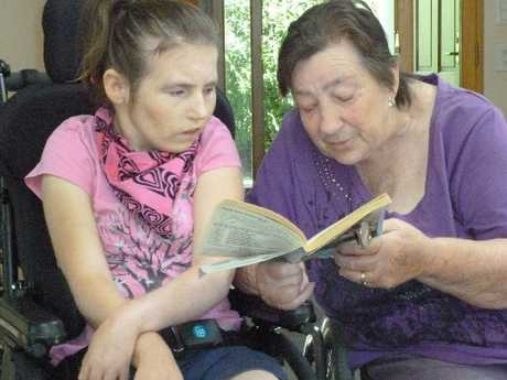 SPECIAL TIME: IHC volunteer Glennys McFelim reads to Karen Thompson.