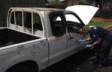 A police scenes of crime officer dusts a stolen ute for finger prints after it was torched in Bridge St.