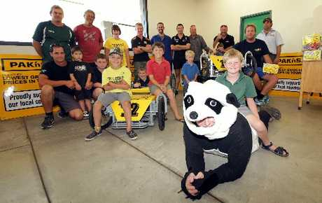 THE GANG'S ALL HERE: Sam Reu, 6, sits on the Garmac Panda, aka Sam Doyle, along with the other winners and organisers of the Pak'n Save Wanganui Soap Box Derby. PHOTO/STUART MUNRO