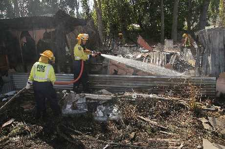 GUTTED: Firefighters douse the smouldering remains of a storage shed which caught fire in Mills Rd, Marshland.