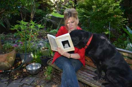 AUTHOR: Lynette Robinson with her book Where The Rainbow Fell Down as her biggest fan, Blakey, looks on.