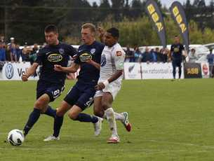 Auckland City defender Simon Arms, middle, brings down Roy Krishna which led to a red card.