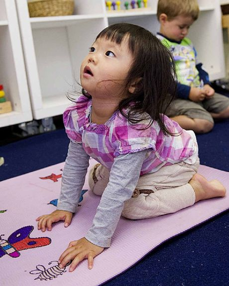 Hanna Soe-Yoshida practises her lion pose during her yoga class at day care.