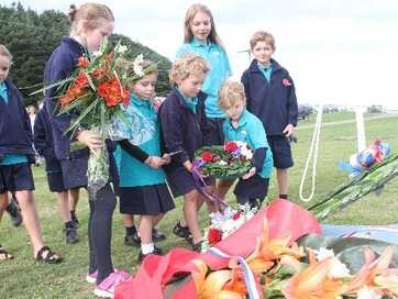 Pirinoa School pupils lay wreaths at the flagstaff in the Wairarapa town of Lake Ferry during its Anzac Day service.