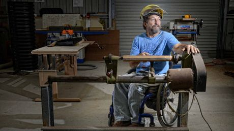 ADAPTING TO NEED: Dave Hawkings sits at the lathe at the Lower Clarence U3A Men's Shed. A bracket was made to lower the lathe so Dave could work at it while in his wheelchair. Photo: Adam Hourigan