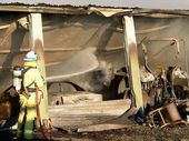 A Gympie Fire and Rescue officer dampens down the scene of yesterdays shed fire on Bath Rd.