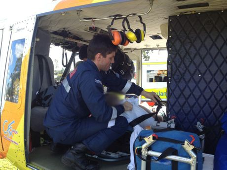 A RACQ CareFlight doctor prepares to airlift a Wandoan man in his 30s after he was seriously wounded by an angle grinder.