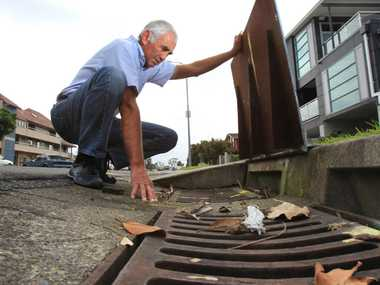 Commons Ave resident Tony Haslett checks one of the offending drains.