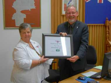 "Motor Caravan Association board member Dawn Fellows presents Whangarei Mayor Morris Cutforth with a certificate awarding the city ""motor home friendly"" status."
