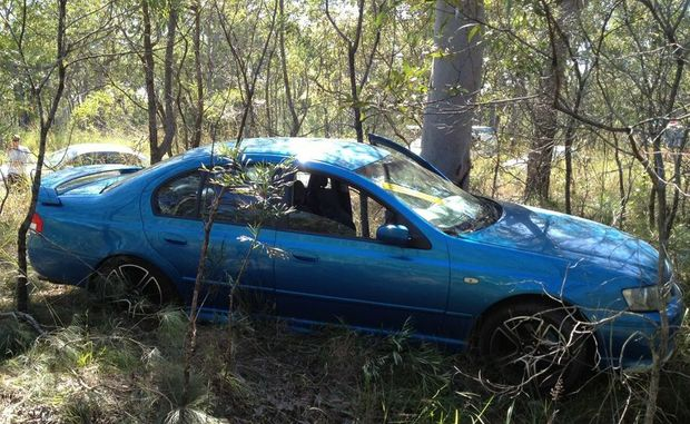 A Ford Falcon came to rest in the bush, narrowly missing a big gum tree, after a crash with a car towing a caravan.