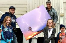 Grant Rolph and his kids Lauren, Chelsea and Charlie deliver the impressive canvas photo of the lightning strike in Pratten (taken by Grant for Higgins Storm Chasing) to Diane Lawlor to use in the monster raffle fundraiser for Pratten residents.