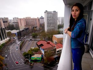 Geraldine Bautista on the 15th floor balcony from which she tried unsuccessfully to save a man who fell 13 storeys outside the Volt apartment block in downtown Auckland. Photo / Dean Purcell