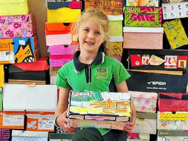 Jasmine O'Neil with her parcel and some of the shoeboxes Cooroy State School students filled for an East Timor school.