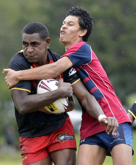 TOUGH TEST: An Ipswich State High School player grabs hold of a Papua New Guinea under-18 footballer during their recent clash.
