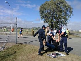 Jim Dowling being arrested outside Western Street Barracks in Rockhampton during Talisman Saber 2013.