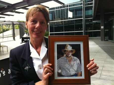 Wamuran's Andrea Mafliet, guidance officer at Woodford, with a photo of her partner Gavin Woods, who was deputy principal at Burpengary State School. He is the subject of an inquest after committing suicide. Bullying is believed to be involved. The photo was taken on one of their happier days. Taken outside Brisbane Magistrates Court.