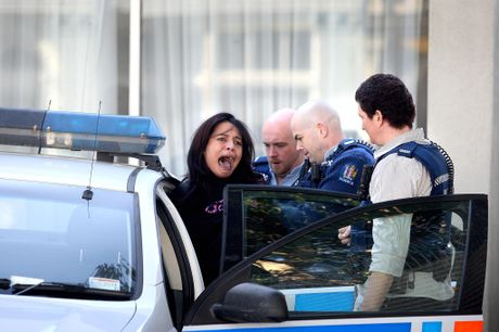 TAKEN AWAY: Kiri Campbell calls to supporters as she is placed in a police car by officers outside Hawera District Court. PHOTOS/BEVAN CONLEY300713WCBRCHAW02A