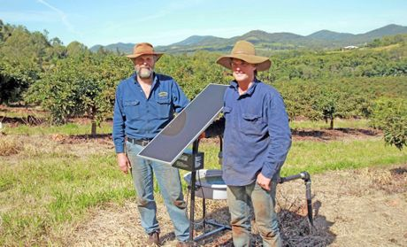 Ian and David Groves with the solar and water systems to reduce bug numbers that can infest crops.