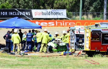 DESPERATE STRUGGLE: Firefighters and paramedics try to rescue the sole survivor of a crash after a private lap session at Queensland Raceway went tragically wrong on Tuesday.
