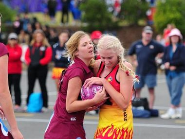 Mackay netball player Bonnie Beckingham (left) fights for the ball against a Bundaberg player.