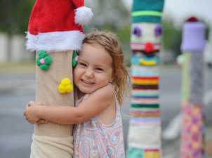 Yarn bombing the Fraser Coast Cultural Centre in Pialba - Three-year-old Piper Dower gives one of the bollard figures a hug.