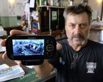 CAUGHT ON CAMERA: Publican Darren Riley with his security monitor.