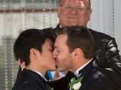 Ivan Hinton (R) and Chris Teoh (L), with marriage celebrant Roger Munson (top-C), are married at Canberra's Old Parliament House on December 7, 2013.