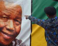 A man points at a portrait of late South African President Nelson Mandela in Soweto on December 10, 2013.
