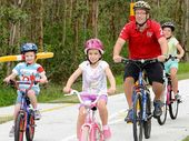PEDAL POWER: Matt Anstey with his children (from left) Simeon, 4, Leah, 6, and Micaela, 8, on the new section of the Goodna Creek Bikeway.