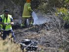 Fire fighters put out a small grass fire as police investigate the accident scene south of Warwick yesterday. Photo Gerard Walsh / Warwick Daily News