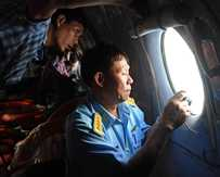 This picture taken from aboard a flying Soviet-made AN-26 used as a search aircraft by Vietnamese Air Force to look for missing Malaysia Airlines flight MH370, shows an officer (R) and a reporter looking out the window during search operations over the southern seas off Vietnam.
