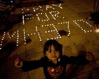 A Malaysian ethnic Chinese child reacts to the camera as others light candles during a vigil for missing Malaysia Airlines passengers at the Independence Square in Kuala Lumpur.