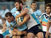 TITANIC RECORD: Gold Coast Titan Luke Douglas wraps up Cronulla's Paul Gallen during his record-breaking 195th consecutive NRL appearance. PHOTO: AAP IMAGE/ACTION PHOTOGRAPHICS, GRANT TROUVILLE