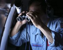 Vietnamese Air Force Colonle Pham Minh Tuan uses binoculars on board an aircraft during a search for the missing Malaysia Airlines flight MH370 in the Gulf of Thailand.