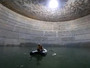 Workers take a raft around LNG tank filled with water