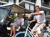 QUIET RIDE: Outrigger staff Nikki Anderson (left) and Matt Gaertner try out the new electric vehicles at Outrigger resort.