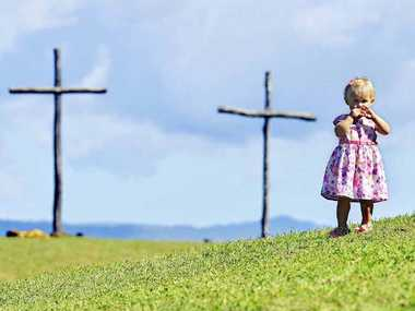 Johanna Christensen, 1, from Tarome, plays on the hill at the Three Crosses on the Hill Good Friday service at Coleyville.