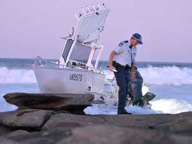A policeman leaves the stricken boat that capsized off Point Cartwright yesterday, tipping all on board into the sea.