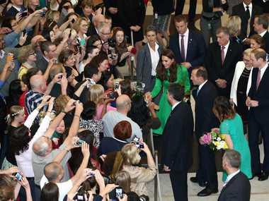 Catherine, the Duchess of Cambridge (C-in green), accompanied by Australia's Prime Minister Tony Abbott (centre R), greets members of the public as her husband Britain's Prince William (far R) looks on, upon their departure from a reception hosted by Abbott at Parliament House in Canberra on April 24, 2014. Britain's Prince William, his wife Kate and their son Prince George are on a three-week tour of New Zealand and Australia. AFP PHOTO / POOL / Alex Ellinghausen