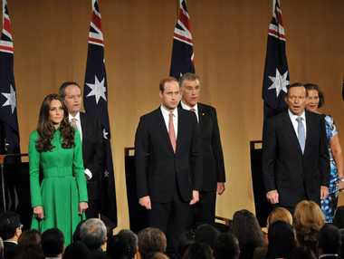 Britain's Prince William (front C) and his wife Catherine, Duchess of Cambridge (R), stand with Australia's Prime Minister Tony Abbott (front R) as they sing the national anthem during a reception at Parliament House in Canberra on April 24, 2014.