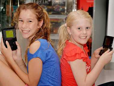 FLASHBACK: Sisters Emma and Sophie Parks compare the original Game Boy to one of the newer versions. The first model they ever played was a Nintendo DS. INSET: Some of the Game Boys over the years.