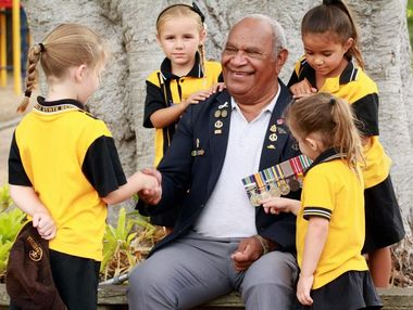 Vietnam Veteran Buddy Lea was honoured by the attention of Granville State school students following their special Anzac Day Service at the school. Pictured with Mr Lea is Baylee Behrendorff, 6, shaking hands, (back left) Abbey Pratt, 5, Kiara Hodges, 4, and looking at the medals Hayley Christie, 5.